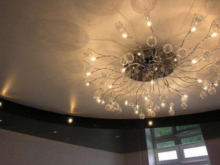 Если предполагается устанавливать глянцевый потолок, помните про отражение и выбирайте люстру, которая смотрится эстетично со всех сторон